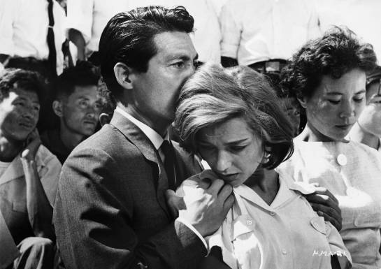 ca. 1959 --- Lui (Eiji Okada) holds Elle (Emmanuelle Riva) in a crowd. --- Image by © John Springer Collection/CORBIS