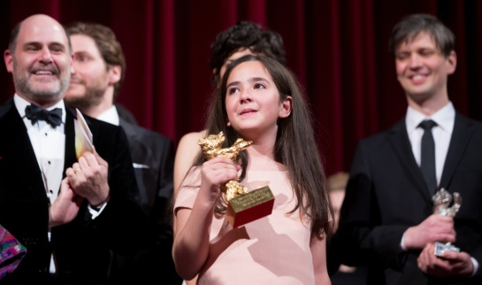 epa04620090 Hana Saeidi (C) holds the Golden Bear for the movie 'Taxi', which she accepted on behalf of Iranian director Jafar Panahi, during the closing and award ceremony of the 65th annual Berlin International Film Festival, in Berlin, Germany, 14 February 2015. The Berlinale runs from 05 to 15 February. EPA/MICHAEL KAPPELER